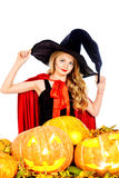 Girl witch. Pretty teen girl with blonde hair in a costume of witch posing with pumpkins. Halloween. Isolated over white background Royalty Free Stock Photo