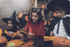 Three children in costumes of fairy-tale monsters on Halloween cut out bats from paper Stock Images