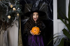 Girl in a witch's costume at a Hallowe'en party, holding a pumpkin Royalty Free Stock Image