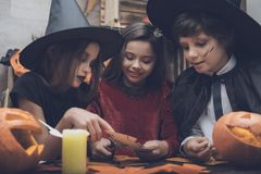 Three children cut out of paper a bat, for a party for Halloween Royalty Free Stock Image
