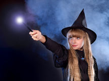 Girl in witch's hat with magic wand. Girl in witch's hat with magic wand casting spells royalty free stock photo