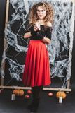 Girl the witch standing in front of black wall in a blouse and red skirt for Halloween with candle. Girl the witch standing in front of black wall with spider royalty free stock photography