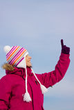 Girl in witer clothes pointing upwards Royalty Free Stock Photo