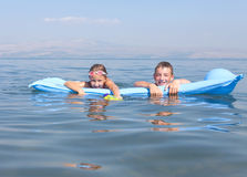 Girl With A Boy On A Mattress Swim Royalty Free Stock Photography
