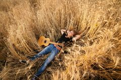 Free Girl With A Guitar Lying In The Wheat Field, Royalty Free Stock Photo - 53828195
