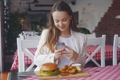 Free Girl With A Long Hair Sitting In A Restaurant. Girl Food Blogger Takes A Picture On The Phone From Social Networks Royalty Free Stock Photo - 152598505