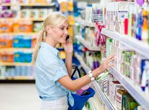 Free Girl With Cellphone At The Shop Choosing Cosmetics Stock Image - 41586471