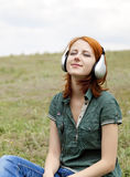 Girl With Headphones At Grass In Spring Time. Stock Photos