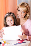 Girl With Mother Holding A White Sheet Of Paper Royalty Free Stock Image
