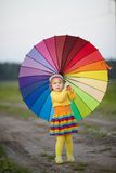 Girl With Rainbow Umrella In The Field Stock Photo