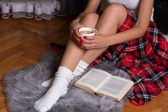 Girl With Sexy Legs Holding A Cup Of Coffee. A Woman Sitting On A Cozy Carpet And Warming With A Plaid Blanket And Book On The Flo Royalty Free Stock Images