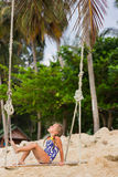 Girl With Two Braids In A Bathing Suit On A Swing On The Beach Royalty Free Stock Photos