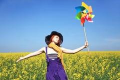 Girl With Wind Turbine At Rape Field.