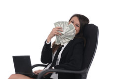 Girl withnetbook and money in chair Royalty Free Stock Photo