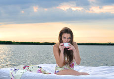 The girl woke up in a bed on water and drink cup of coffee Royalty Free Stock Photos