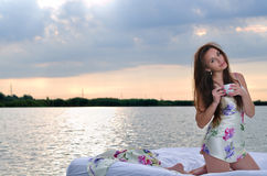 The girl woke up in a bed on water and drink cup of coffee. Royalty Free Stock Photography