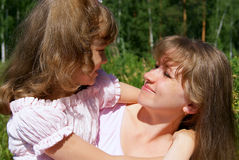 The girl and the woman. In the summer on the nature the daughter with mother having embraced look against each other Royalty Free Stock Images