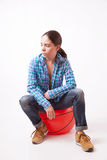 Girl woman in a blue shirt and jeans sitting on the ball Stock Photos