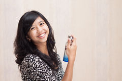 Beautiful Asian girl with perfume. Girl or woman caring her smell Royalty Free Stock Photography