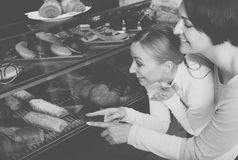 Girl and woman gladly selecting pastry Stock Image