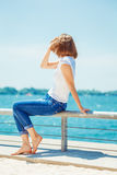 Girl woman in jeans sitting near water Stock Image