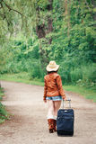 Girl woman in leather jacket, blue denim shorts, straw hat, standing walking on country road wild forest with travel bag Stock Photos
