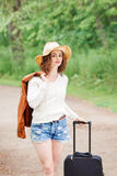 Girl woman in leather jacket, blue denim shorts, straw hat, standing walking on country road wild forest with travel bag Stock Images