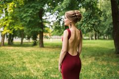 Girl, woman in a long waist-fitting festive evening dress with bare back stands in a green park. Garden, with a beautiful hairdo Stock Photo