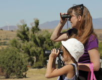 A Girl and a Woman Look Through Binoculars Royalty Free Stock Images