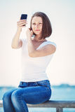 Girl woman looking at cell phone making selfie Stock Images