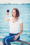 Girl woman looking at cell phone making selfie Stock Photos