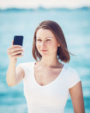 Girl woman looking at cell phone making selfie Royalty Free Stock Photography