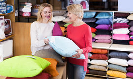 Girl and woman looking for pillow stock photos