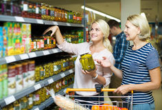 Girl and woman purchasing canned food at supermarket. Happy russian girl and mature women purchasing canned food at supermarket Stock Images