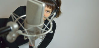 Girl, woman in a recording Studio composes a song. The girl in earphones and microphone Royalty Free Stock Image