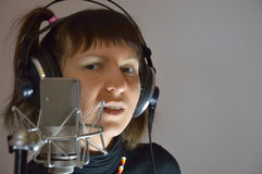 Girl, woman in a recording Studio sing a song. The girl in earphones and microphone Stock Photography