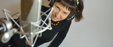 Girl, woman in a recording Studio sing a song. The girl in earphones and microphone Royalty Free Stock Image