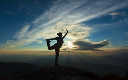 Girl or woman silhouette posing in sunset mountain landscape. royalty free stock photography