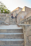 Girl and woman sit on old yellow stone staircase of limestone in the Santa Barbara castle, Alicante, Spain. Old yellow stone staircase of limestone in the of Royalty Free Stock Photos