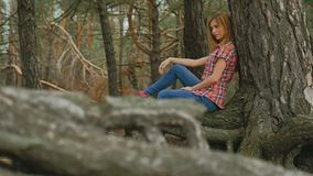 Girl woman sits in large pine tree forest roots slow motion stock footage