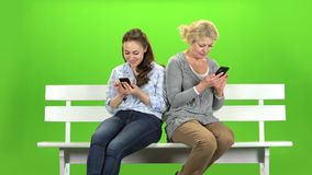 Girl and a woman are sitting on a bench and looking at the phones. Mobile dependency. Green screen.  stock video footage