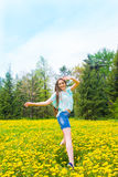 Girl (woman) in summer park. Beautiful joyful happy attractive carefree young girl (woman) dancing and jumping in summer (spring) park on yellow dandelions Royalty Free Stock Photo
