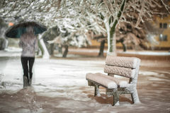 Girl or woman walking on the strees with umbrella in snowstorm, bench with snow in the city, night photography Royalty Free Stock Image