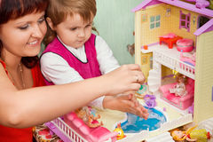 Girl and woman washes doll in pool of toy house Royalty Free Stock Photography
