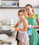 Girl  with woman washing dishes Stock Image