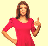 Girl woman young positive sign thumbs yes in pink dress isolated Stock Image