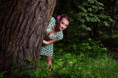 Girl in the wood. Girl peeking from behind the tree Royalty Free Stock Image