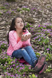 Girl in the wood sneezing because of the flowers Royalty Free Stock Image