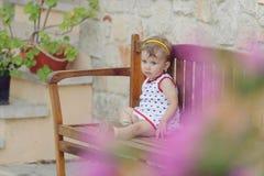 Girl on Wooden Bench Stock Photos