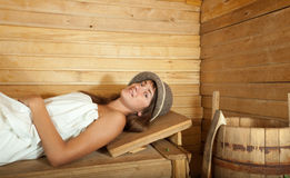 Girl  on wooden bench in sauna Royalty Free Stock Photo